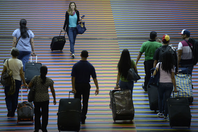 People walk with their luggage at the Maiquetia international airport that serves Caracas on July 3, 2014. A survey by pollster Datanalisis revealed that 25% of the population surveyed (end of May) has at least one family member or friend who has emigrated from the country. AFP PHOTO/Leo RAMIREZ