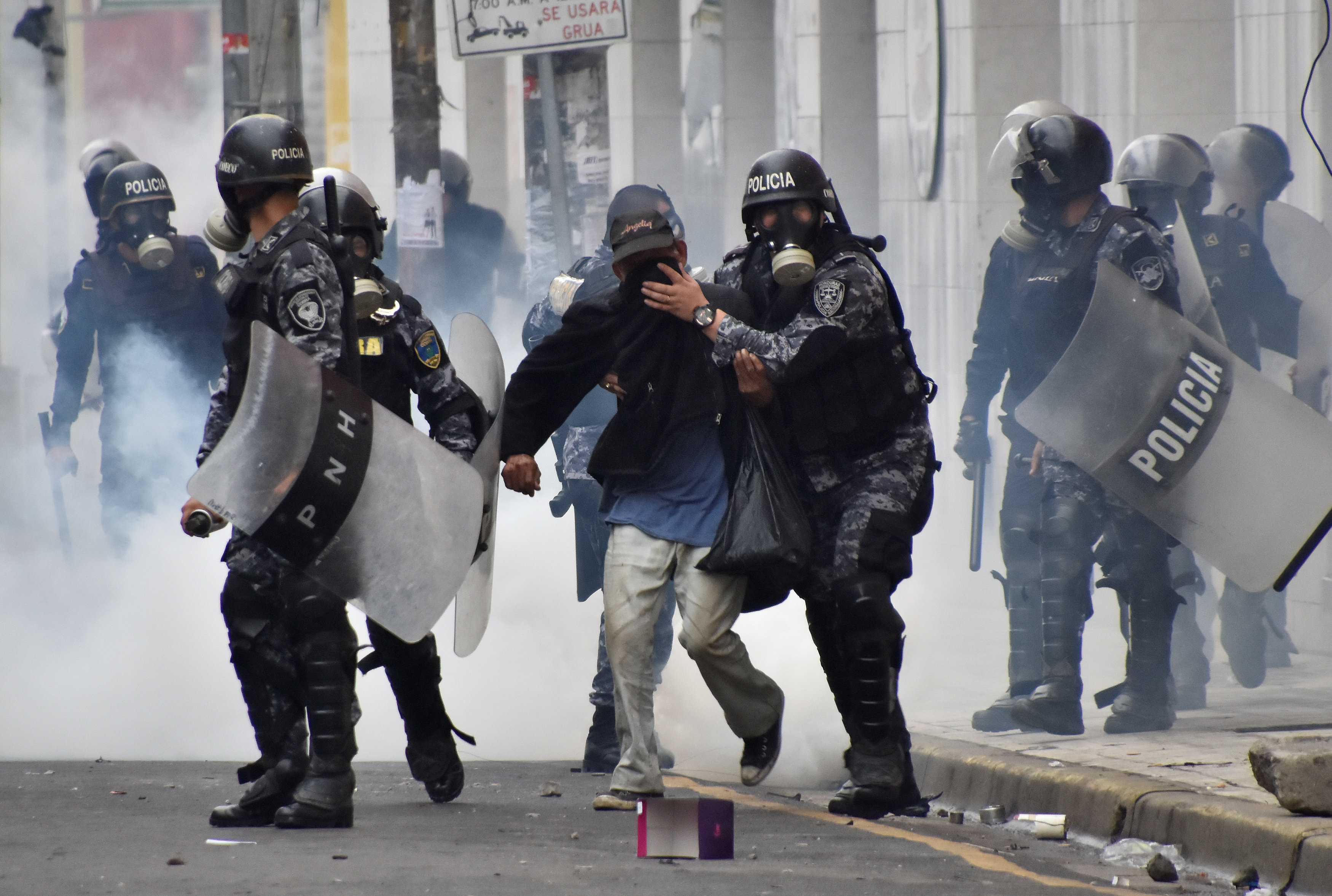 Police help a pedestrian overcome by tear gas as supporters of Salvador Nasralla, presidential candidate for the Opposition Alliance Against the Dictatorship, clash with police during a protest caused by the delayed vote count for the presidential election in San Pedro Sula, Honduras December 1, 2017. REUTERS/Moises Ayala