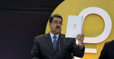 "Venezuela's President Nicolas Maduro reads a document during the event launching the new Venezuelan cryptocurrency ""Petro"" in Caracas, Venezuela February 20, 2018. REUTERS/Marco Bello"