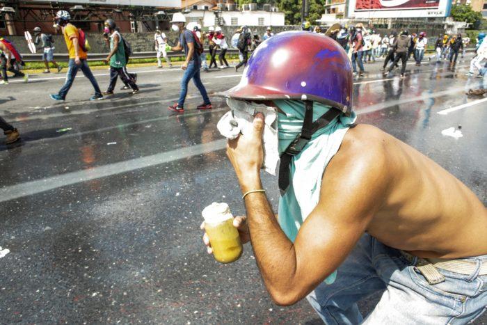 """CAR47. CARACAS (VENEZUELA), 10/05/2017 - Un manifestante arroja una bomba de heces a a la Guardia Nacional Bolivariana hoy, miércoles 10 de mayo de 2017, en Caracas (Venezuela). Los manifestantes que desde hace más de un mes han salido a las calles de Venezuela para protestar en contra del Gobierno de Nicolás Maduro, han encontrado otra forma de afrontar a los funcionarios de seguridad al lanzarles tarros de excremento, que hoy se conocen como """"puputov"""". EFE/CRISTIAN HERNÁNDEZ"""